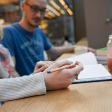 Student taking notes in a cafe